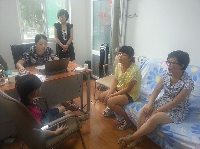 验配师和家长在配合检验孩子戴助听器的效果