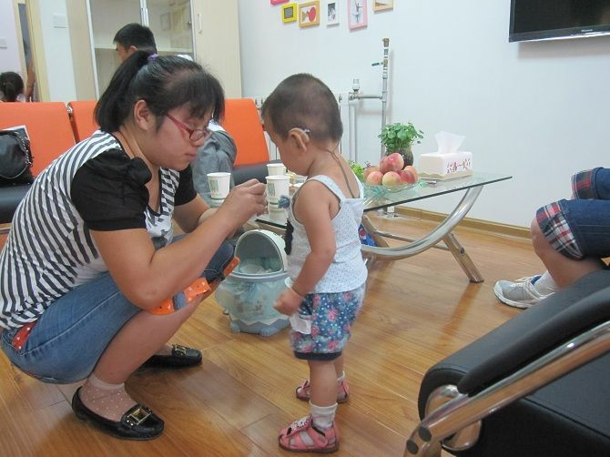 孩子家长为自己的宝宝佩戴助听器