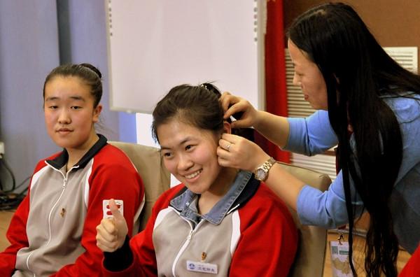 自然之声长安街助听器验配中心验配师王利华老师为孩子们佩戴助听器
